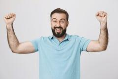 Szczęśliwy brodaty mężczyzna podnosi jego ręki pokazuje zwycięstwo gestykuluje blisko biel ściany Przystojny facet właśnie wygryw Fotografia Stock