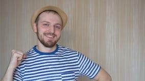 Szczęśliwy brodaty mężczyzna w kapeluszowym falowaniu z jego ręką zbiory wideo