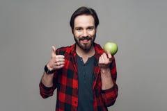 Szczęśliwy brodaty mężczyzny chwyt Apple i patrzeć kamerę zdjęcia royalty free