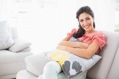 Szczęśliwy brunetki obsiadanie na jej kanapie ono uśmiecha się przy kamerą obrazy royalty free