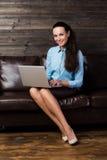 Szczęśliwy brunetki obsiadanie na kanapie w żywym izbowym używa laptopie Zdjęcie Stock