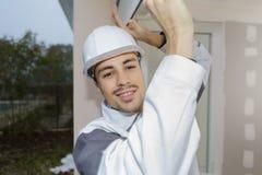 Szczęśliwy budowniczy ustawia dopasowania na okno Fotografia Stock