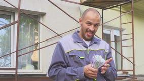 Szczęśliwy budowniczy z mnóstwo dolara pieniądze outdoors Pojęcie sukces w budowie zbiory