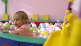 Szczęśliwy caucasian śliczny blondynki dziecko ma zabawę i bawić się w wielo- coloured balowym basenie preschool zbiory