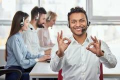 Szczęśliwy centrum telefoniczne pracownik daje ok gestom Zdjęcia Stock
