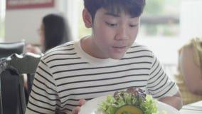 Szczęśliwy chłopak z Azji lubi jeść obiad w restauracji z uśmiechem zbiory wideo
