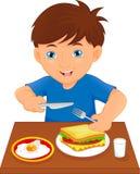 Szczęśliwy chłopiec łasowanie przy stołem ilustracja wektor