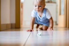 Szczęśliwy chłopiec czołganie chwytać pacyfikator w domu fotografia stock