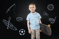 Szczęśliwy chłopiec czuć ufny podczas gdy stojący z nowy deskorolka zdjęcie stock