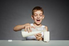 Szczęśliwy chłopiec dolewania mleko w szkło zdjęcie royalty free