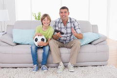 Szczęśliwy chłopiec dopatrywania mecz piłkarski z ojcem na kanapie Zdjęcia Royalty Free