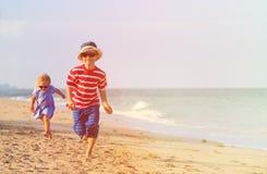 Szczęśliwy chłopiec i dziewczyny bieg na piasku wyrzucać na brzeg zdjęcia royalty free
