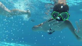 Szczęśliwy chłopiec nur w basenie i patrzeć kamerę, podwodny krótkopęd, słońce promienie zbiory wideo