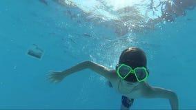 Szczęśliwy chłopiec nur w basenie i patrzeć kamerę, podwodny krótkopęd, słońce promienie zbiory