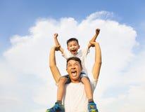 Szczęśliwy chłopiec obsiadanie na ojca ramieniu Zdjęcia Royalty Free