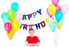 Szczęśliwy chłopiec obsiadanie przy stołem w przyjęciu urodzinowym zdjęcia stock