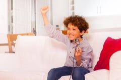 Szczęśliwy chłopiec odświętności zwycięstwo, bawić się wideo gry fotografia royalty free