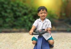 Szczęśliwy chłopiec przejażdżki zabawki samochód Figlarnie dzieciak przy boiskiem Fotografia Royalty Free