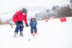 Szczęśliwy chłopiec uczenie narciarstwo z jego ojcem w Kitzbuhel ośrodku narciarskim, Tyrol, Austria Fotografia Stock