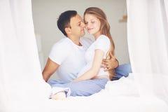 Szczęśliwy ciężarny pary obejmowanie w sypialni w ranku Obrazy Stock