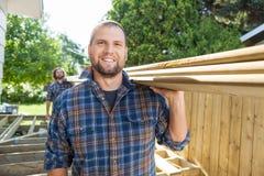 Szczęśliwy cieśli I Coworker przewożenie Lumbers Przy obraz royalty free