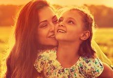 Szczęśliwy cieszy się macierzysty przytulenie jej figlarnie roześmiana dzieciak dziewczyna w zmierzchu pogodnym świetle na lata t zdjęcia royalty free