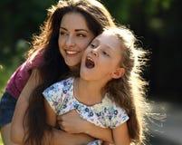 Szczęśliwy cieszy się macierzysty przytulenie jej relaksująca uśmiechnięta dzieciak dziewczyna na b Zdjęcia Stock