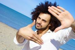 Szczęśliwy cool mężczyzna bawić się z kamerą na plażowy pozować zdjęcia royalty free