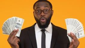 Szczęśliwy czarny żłób w kostiumu trzyma wiązki dolary, inwestycji kapitałowej bogactwo zbiory