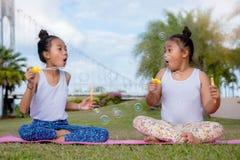 Szczęśliwy czas przyjaźń, dwa dziewczyn dzieciaka siostrzanej sztuki mydlany bąbel Smil obrazy stock