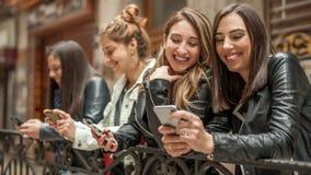 Szczęśliwy cztery przyjaciela ogląda internetów ogólnospołecznych środki w telefonie komórkowym obraz stock