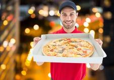 Szczęśliwy deliveryman pokazuje pizzę w mieście przy nocą światła obraz stock