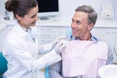 Szczęśliwy dentysty mienia narzędzie podczas gdy patrzejący mężczyzna Obraz Stock