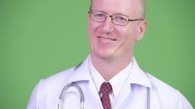 Szczęśliwy dojrzały łysy mężczyzna lekarki główkowanie przeciw zielonemu tłu zbiory wideo