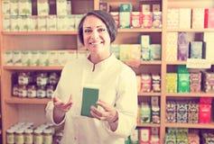 Szczęśliwy dojrzały żeński sprzedawca trzyma żywienioniowe odżywki obrazy royalty free