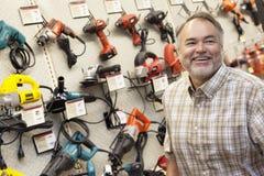 Szczęśliwy dojrzały narzędzia właściciel sklepu patrzeje daleko od Obrazy Stock