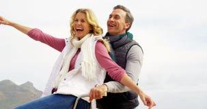 Szczęśliwy dojrzały pary obsiadanie na bicyklu z rękami szeroko rozpościerać zbiory wideo
