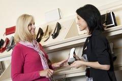 Szczęśliwy dojrzały sprzedawca z w połowie dorosłym klientem w obuwianym sklepie Zdjęcie Stock