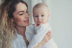 szczęśliwy dom rodzinny Macierzysty mienia dziecka syn w sypialni w wygodnym weekendzie obrazy royalty free