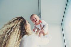 szczęśliwy dom rodzinny Macierzysty mienia dziecka syn w sypialni w wygodnym weekendzie obraz royalty free
