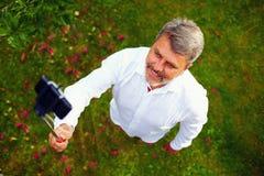 Szczęśliwy dorośleć mężczyzna bierze selfie na telefonie Fotografia Royalty Free