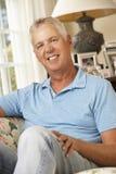 Szczęśliwy Dorośleć mężczyzna obsiadanie Na kanapie W Domu obrazy stock