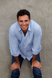 Szczęśliwy dorośleć mężczyzna ono uśmiecha się z rękami na kolanach obrazy stock