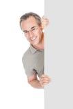 Szczęśliwy dorośleć mężczyzna pozycję za plakatem Obrazy Royalty Free