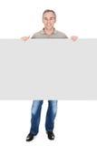 Szczęśliwy dorośleć mężczyzna pozycję za plakatem Fotografia Royalty Free