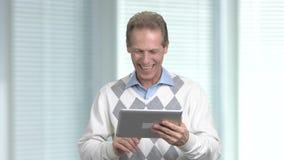 Szczęśliwy dorośleć mężczyzna używa komputer osobisty pastylkę zbiory wideo