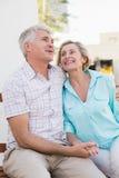 Szczęśliwy dorośleć pary obsiadanie na ławce w mieście Zdjęcia Stock