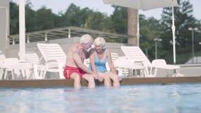 Szczęśliwy dorośleć pary obsiadanie na krawędzi basenu Śliczny starszego mężczyzny i kobiety relaksujący przytulenie w hotelowym  zbiory wideo