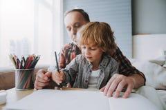 Szczęśliwy dziad i mały wnuk malujemy z kolorami obraz royalty free