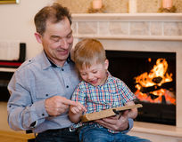 Szczęśliwy dziad i wnuk czyta książkę Obrazy Royalty Free